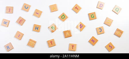Scattered alphabet letters wooden blocks tiles on white table background. Top view - Stock Photo