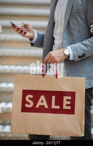 Close up of fashionable man holding shopping bags with SALE inscription while using smartphone in mall, copy space - Stock Photo