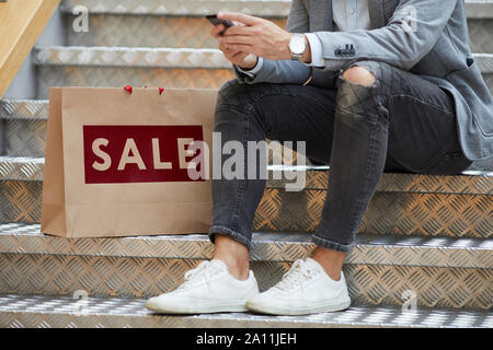 Closeup of fashionable young man using smartphone sitting on stairs in mall, shopping bags with SALE inscription beside him, copy space - Stock Photo