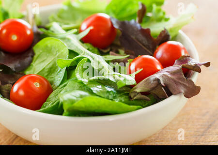 Salad in a white bowl with lettuce and tomatoes - Stock Photo