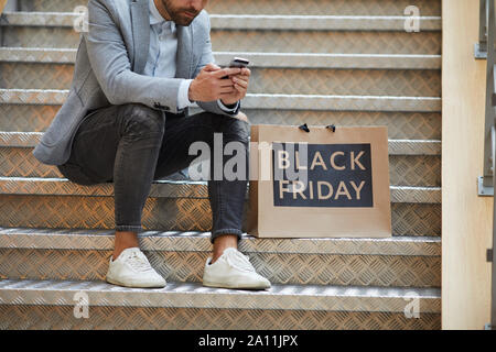 Cropped portrait of fashionable young man using smartphone sitting on stairs in mall, shopping bags with SALE inscription beside him, copy space - Stock Photo