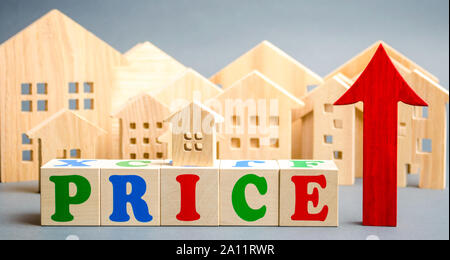Wooden blocks with the word Price, up arrow and wooden houses. The concept of raising property prices. High cost for rental housing and real estate. E - Stock Photo