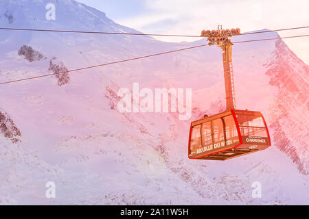 Chamonix Mont Blanc, France - January, 28, 2015: Cable Car from Chamonix to the summit of the Aiguille du Midi and pink sunset snow mountains panorama - Stock Photo