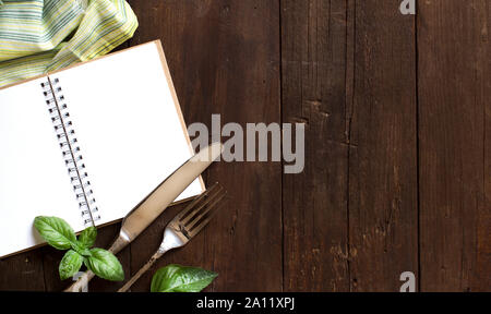 Blank cooking recipe book with fork, knife, basil and napkin on a wooden table - Stock Photo