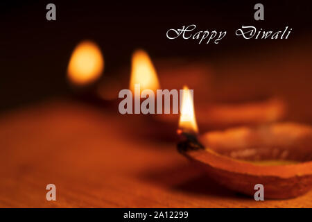 Beautiful blurred background stock photo of Diwali Diya or oil clay lamp with Happy Diwali text and copy space isolated on black background. - Stock Photo