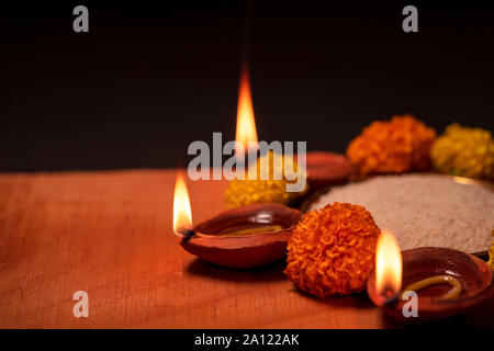 Happy Diwali wishing with clay diya or oil lamp decorated traditionally with flowers and rice in a bowl. Background concept for diwali with copy space - Stock Photo