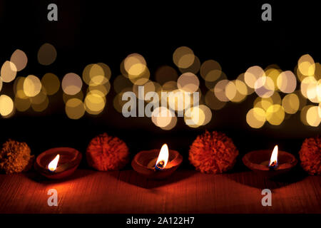 Dark moody diya or terracotta lamp lit in a row during Diwali Indian Hindu Festival with bokeh light isoltaed on black background. - Stock Photo
