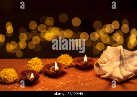 Happy Diwali background - Colorful Clay Diya lit during Deepavali festival on black backdrop with bokeh lights & copy space. - Stock Photo