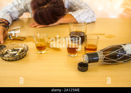 drunk depressed girl leaning against the table with glasses still full - Stock Photo