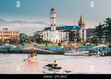 Batumi, Adjara, Georgia - September 10, 2017: Motorized Hang Glider Landing On Sea Near Chacha Tower In Sunny Summer Day. - Stock Photo