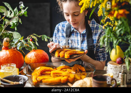 A woman chef holding slices of baked orange pumpkin with honey and cinnamon at a wooden table. Concept autumn food in a cozy kitchen with flowers. - Stock Photo