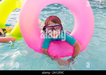 siblings playing in pool with colorful floaties. - Stock Photo