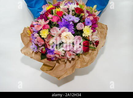 beautiful bouquet with different flowers of roses and chrysanthemums in the hands of a man. Colorful bouquet of different fresh flowers, close-up - Stock Photo