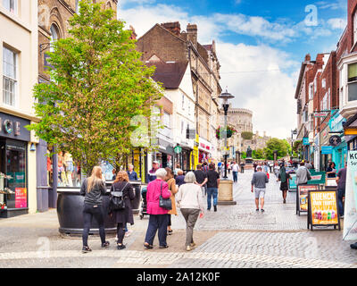 5 June 2019: Windsor, Berkshire, UK - Shoppers and tourists in Peascod Street, the main shopping street in the town, with Windsor Castle at the top... - Stock Photo