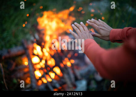 Young woman making fire while camping outdoors, in an alpine wilderness - warming up her hands near the fire - Stock Photo