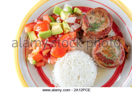 Fusion cuisine depicting the Cuban pork fillet covered in bacon and the Mexican 'Pico de Gallo' salad. The dish has white basmati rice as side dish - Stock Photo