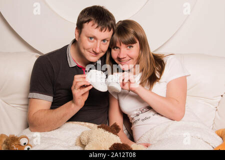 Zaporizhia, Ukraine - April 5, 2012: Portrait of happy future parents. The pregnant woman and the future father are holding little baby shoes - Stock Photo