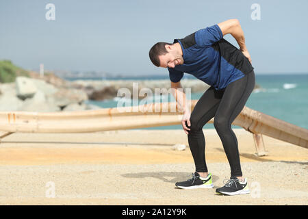 Painful runner complaining suffering back ache after sport on the beach - Stock Photo