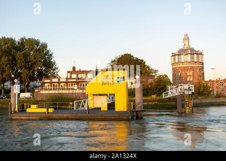 Docking quay and scaffolding on the river Maas in Rotterdam port area for pleasure boats with a water tower in the background at sunset - Stock Photo
