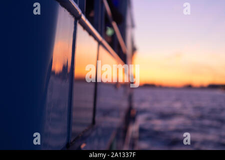 Reflection of a colourful orange and purple sunset in the window panes of a party boat on the river Maas in Rotterdam with the cityscape out of focus - Stock Photo