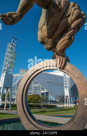 Mercedes-Benz Stadium seen through the Olympic ring of The Flair bronze sculpture by Richard MacDonald at Georgia International Plaza in Atlanta, GA. - Stock Photo
