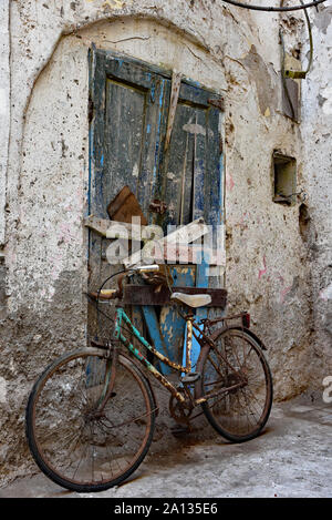 Old, rusty bicycle parked against a dilapidated Moroccan door to a typical lime-washed wall in the quintessential town of Essaouira, Morocco, Africa. - Stock Photo