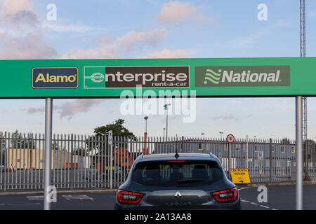 Alamo, Enterprise and National signs at a car rental depot - Manchester Airport Car Rental Village, UK - Stock Photo