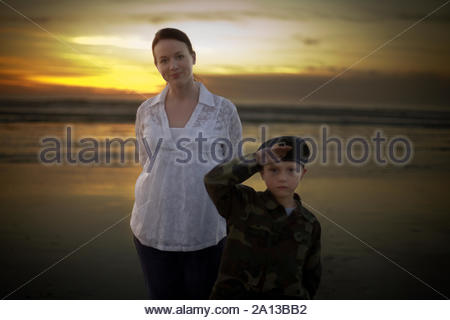 Portrait of a small boy with his mother on a beach. - Stock Photo