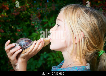 Portrait of preteen adorable child girl playing with her pet giant African snail (Achatina fulica). Concept of not to be afraid of unusual animals. - Stock Photo