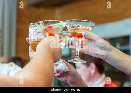 Cheers. Group of people drinking and toasting in restaurant. Hands holding glasses of champagne and wine making toast. Christmas new year wedding holiday party time. Celebration and nightlife concept - Stock Photo