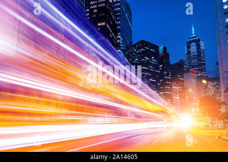 Busy traffic and urban landscape at night in Hong Kong - Stock Photo