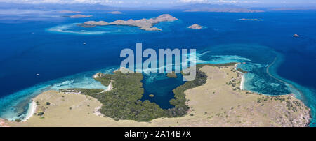 Bird's eye view shows scattered islands and fringing reefs in Komodo National Park, Indonesia. - Stock Photo