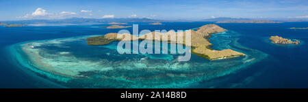 Bird's eye view shows idyllic islands and fringing reefs in Komodo National Park, Indonesia. - Stock Photo