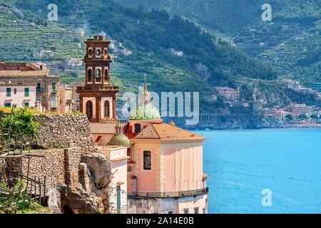 The brown bell tower, tiled domes, and pink rear exterior of the Collegiate Church of St. Mary Magdalene, in Atrani, Italy, on the Amalfi Coast. - Stock Photo