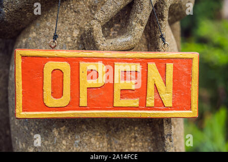 Plate open on a red background in a tropical garden - Stock Photo