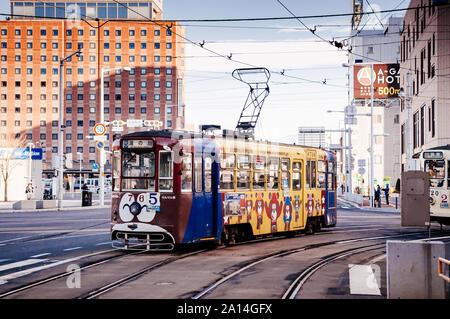 DEC 2, 2018 Hakodate, JAPAN - Hakodate city tram vintage streetcar approaching station near JR train station. The Tram well-established network throug - Stock Photo