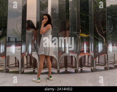Teen in grey dress standing in front of multiple mirrors facing camera - Stock Photo