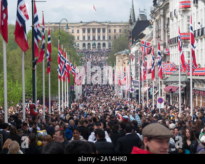 Oslo, Norway - May 17 2010: The crowd celebrating the national day and the Palace of the king. - Stock Photo