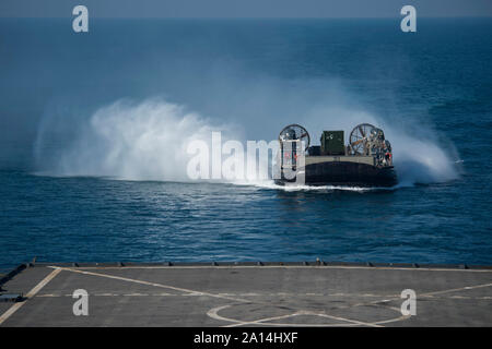 A Landing Craft Air Cushion makes its approach to the well deck of USS Comstock. - Stock Photo