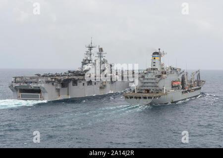 USS Iwo Jima conducts an underway replenishment with USNS Patuxent. - Stock Photo