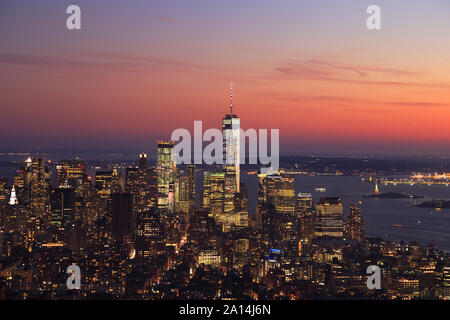 Aerial view of New York City, Lower Manhattan skyline illuminated at sunset including One World Trade Center and Liberty Island, USA