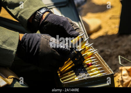 A Marine Explosive Ordnance Disposal technician prepares to stage .50 Caliber rounds. - Stock Photo