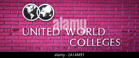 The Logo and name of the United World Colleges on the background of a pink brick wall - Stock Photo