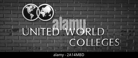 The Logo and name of the United World Colleges on the background of a grey brick wall - Stock Photo