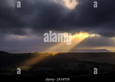 Sunbeams breaking through the clouds over downland - Stock Photo