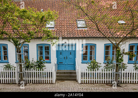Old danish house with blue windows and a white fence in the island of Aero, Ærøskøbing , Denmark, July 13, 2019