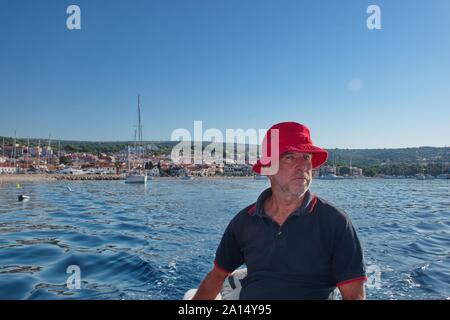 Portrait of senior man driving the boat with Primosten cityscape in the background - Stock Photo