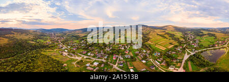 180 degrees panoramic landscape of countryside, aerial drone view of urban village Pidbuzh in Carpathians, Ukraine. Sunset time, end of summer. - Stock Photo