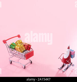 Christmas shopping concept, mini red shop cart trolley with Santa Claus toy and gift box isolated on pale pink background, blank copy space, close up - Stock Photo