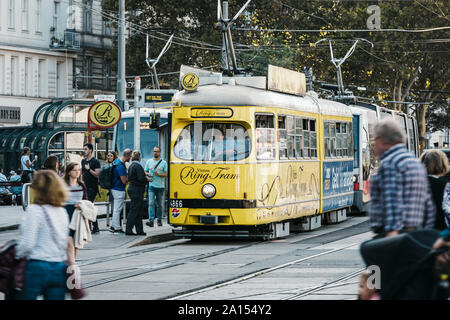 Walking people and old style tram on the street of Vienna - federal capital and largest city of Austria. - Stock Photo